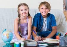 Menino e irmã que estudam com livros Imagens de Stock