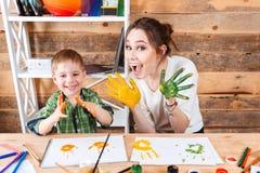 Menino e mãe de sorriso que mostram as mãos pintadas em pinturas coloridas Imagens de Stock Royalty Free