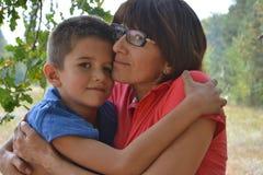 Menino e mãe que abraçam na floresta Imagem de Stock Royalty Free