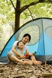 Menino e matriz que sentam-se pelo acampamento Fotografia de Stock Royalty Free