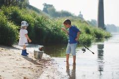 Menino e menina com a haste na costa do rio imagem de stock royalty free