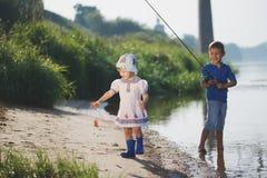 Menino e menina com a haste na costa do rio fotografia de stock royalty free