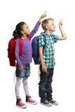 Menino e menina de escola com apontar das trouxas Fotografia de Stock Royalty Free