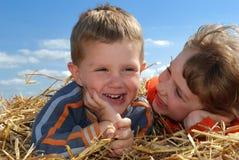 Menino e menina de sorriso no close-up da palha ao ar livre Fotografia de Stock