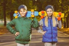 Menino e menina de sorriso que guardam a moeda de um centavo do plástico da cor Fotografia de Stock Royalty Free