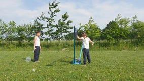 Menino e menina do jovem adolescente que jogam o badminton no prado com a floresta no fundo Crianças com as raquetes de badminton vídeos de arquivo