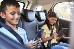 Menino e menina em um carro usando tabuletas durante a viagem por estrada da família foto de stock royalty free