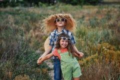 Menino e menina em uma caminhada do verão no campo imagens de stock