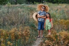Menino e menina em uma caminhada do verão no campo imagem de stock royalty free