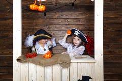 Menino e menina engraçados em trajes do pirata no estúdio com cenário para Dia das Bruxas Imagens de Stock Royalty Free