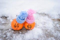 Menino e menina expressões faciais engraçadas nas tangerinas imagens de stock