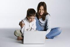 Menino e menina felizes com computador portátil Fotografia de Stock