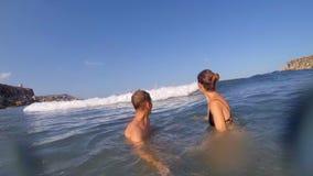Menino e menina felizes nas férias de verão que têm o divertimento na água Malta o conceito de umas férias de verão alegres video estoque
