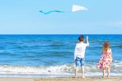 Menino e menina na praia com um papagaio Conceito da liberdade carefree foto de stock
