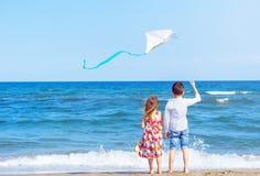 Menino e menina na praia com um papagaio Conceito da liberdade carefree imagens de stock