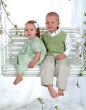 Menino e menina no balanço Fotografia de Stock Royalty Free