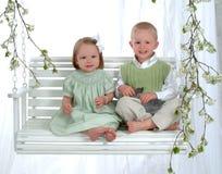 Menino e menina no balanço com coelho foto de stock royalty free