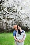 Menino e menina no fundo do abricó de florescência Um indivíduo abraça Fotografia de Stock