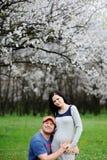 Menino e menina no fundo do abricó de florescência Um indivíduo abraça Fotos de Stock