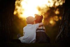 Menino e menina no por do sol foto de stock royalty free