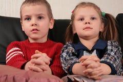 Menino e menina no sofá que prestam atenção à tevê fotos de stock royalty free