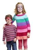 Menino e menina novos com pintura da face do gato e do spiderman Imagens de Stock Royalty Free