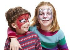 Menino e menina novos com pintura da face do gato e do spiderman Imagem de Stock Royalty Free