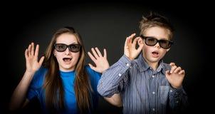 Menino e menina novos com vidros 3D.  Espectadores do cinema. Fotos de Stock Royalty Free