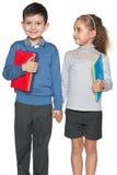 Menino e menina novos de sorriso com livros Fotografia de Stock Royalty Free