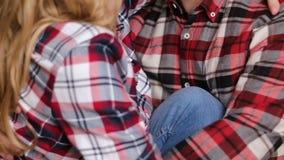 Menino e menina novos dos pares em camisas quadriculado filme
