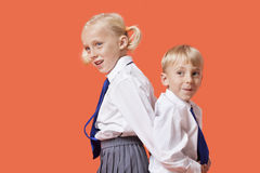Menino e menina novos felizes na farda da escola que está de volta à parte traseira sobre o fundo alaranjado Fotografia de Stock