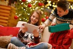 Menino e menina que apreciam em presentes do Natal da música imagem de stock royalty free