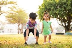 Menino e menina que aprendem a bola do pontapé no parque na noite imagem de stock royalty free