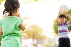 Menino e menina que aprendem a bola do pontapé no parque na noite fotos de stock royalty free