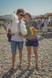 Menino e menina que comem o algodão doce na praia Foto de Stock