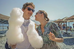 Menino e menina que comem o algodão doce na praia Imagens de Stock