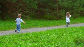 Menino e menina que correm através do parque video estoque