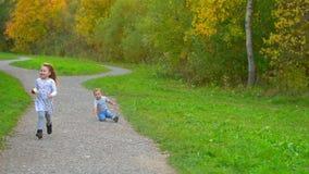 Menino e menina que correm através do parque filme