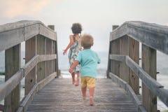 Menino e menina que correm na plataforma de madeira na praia imagem de stock royalty free