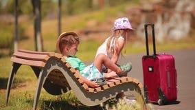 Menino e menina que descansam em um banco com uma mala de viagem video estoque