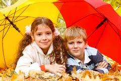 Menino e menina que encontram-se no leafage amarelo Imagens de Stock Royalty Free