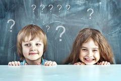 Menino e menina que escondem atrás de uma tabela Foto de Stock