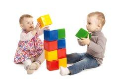 Menino e menina que jogam com cubos Fotos de Stock