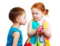 Menino e menina que jogam com móbil Foto de Stock Royalty Free