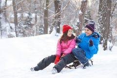 Menino e menina que jogam fora em pequenos trenós Imagem de Stock Royalty Free