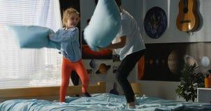 Menino e menina que jogam a luta de descanso na cama foto de stock royalty free