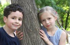 Menino e menina que jogam no parque Fotos de Stock Royalty Free