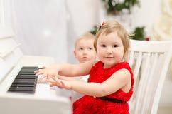 Menino e menina que jogam no piano branco fotografia de stock royalty free
