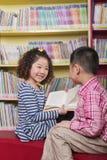 Menino e menina que leem junto Imagem de Stock