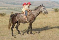 Menino e menina que montam um cavalo na exploração agrícola Imagens de Stock Royalty Free